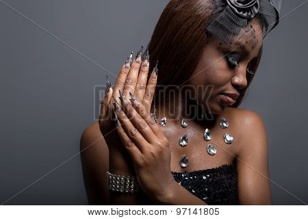 beautiful girl with dark skin and long acrylic nails in a black dress in the studio