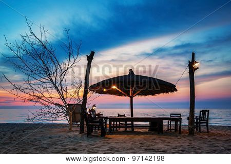 Wooden chairs and umbrella on white beach in sunset time at Phu Quoc island in Vietnam