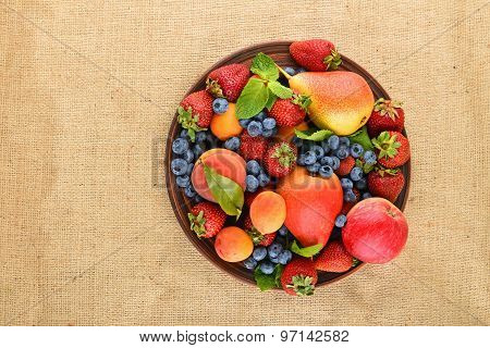Fruits And Berries Mix In Ceramic Plate On Burlap Canvas