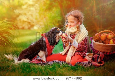 happy child girl playing with her dog and giving hin apple in autumn garden