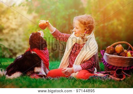 happy child girl having fun training her dog with apple in autumn garden