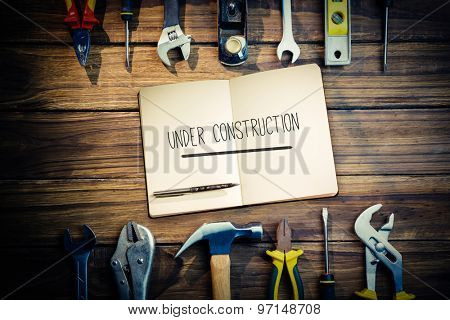 The word under construction and notebook and pen against desk with tools