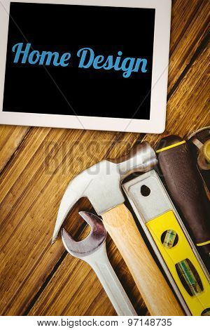 The word home design and tablet pc against desk with tools