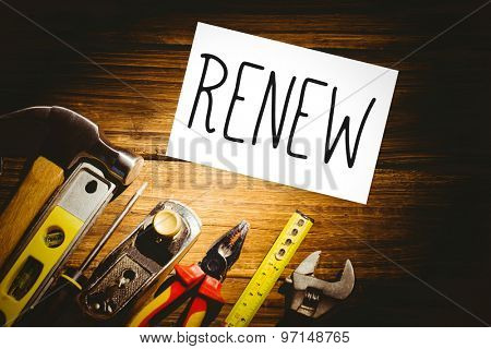 The word renew and white card against desk with tools