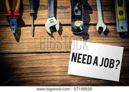 The word need a job? and white card against desk with tools