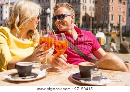 Young cheerful couple drinking Aperol Spritz cocktail in cafe