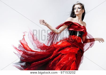 Fashion photo of young magnificent woman in red dress. Studio portrait