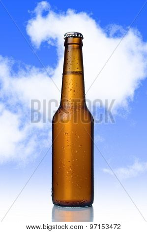 Golden Beer With Frost Bubbles In Brown Glass Bottle Isolated On Blue Sky