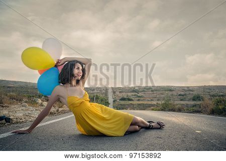 Woman in a yellow dress lying on the street