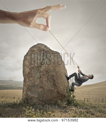 Manager climbing a rock with the help of someone