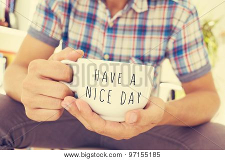 closeup of a young man with a cup of coffee or tea in his hand with the text have a nice day written in it