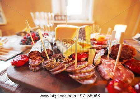 Various sliced sausage and cheese on table