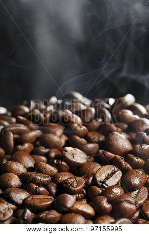 Hot roasted coffee beans and steam on black