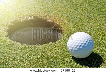 Golf Ball Next To A Hole