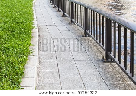 Concrete pathway and metal fence at riverside