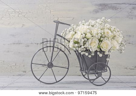 White roses in a bicycle vase