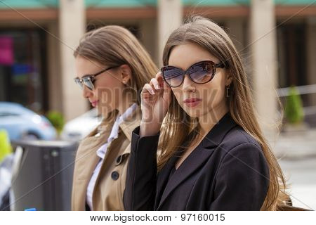 Two young beautiful business women in sunglasses in the summer city