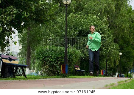 Happy young man in a green shirt and blue jeans running on summer park
