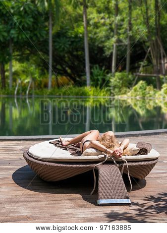 Young beautiful girl resting by the swimming pool