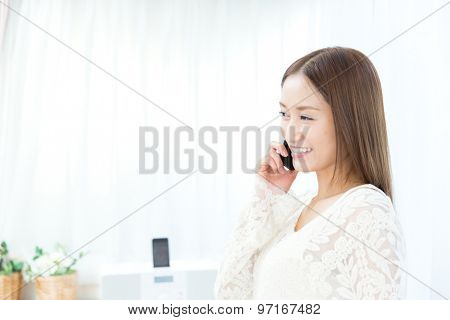 Beautiful asian woman using a cellular in the room