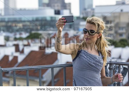 Young beautiful blonde in sunglasses taking a selfie on smartphone.