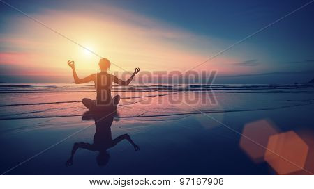 Silhouette of woman practicing yoga with the reflection on the wet sand during surrealistic sunset at the seaside.