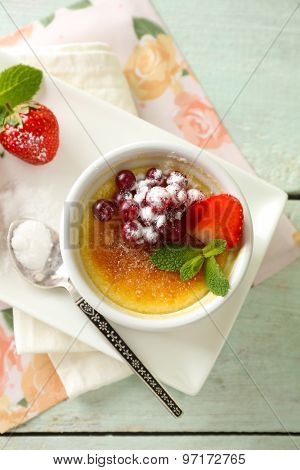 Creme brulee dessert with fresh strawberries and mint leaves, on color wooden background