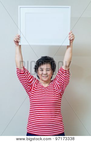 Asian Woman Holding Empty White Picture Frame In Studio Shot, Specialty Tone