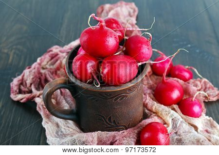 Red radish in clay cup on wooden table with scarf, closeup