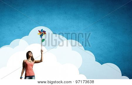 Happy young woman with windmill in hand