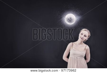Young pretty smiling woman looking at moon