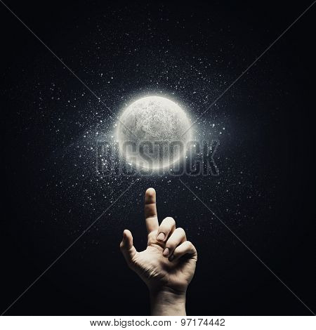 Man's hand pointing at moon with finger