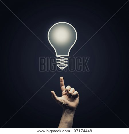 Human hand pointing with finger at light bulb