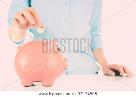 Woman inserting money into piggy bank close up