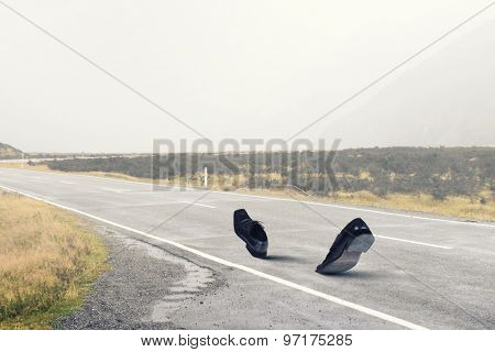 Pair of black shoes walking on road