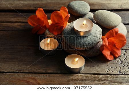 Beautiful spa composition with candles and flowers on wooden table close up