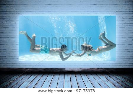 Cute couple holding hands underwater in the swimming pool against room with screen