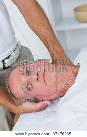 Man receiving neck massage in medical office