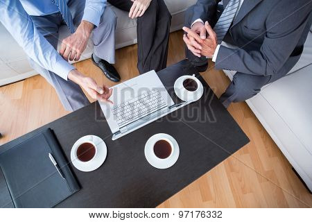 Three business people with laptop and diary at office