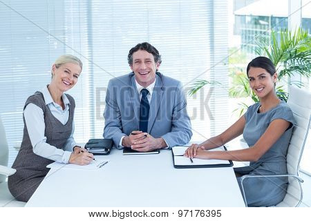 Smiling business people looking at camera in an office