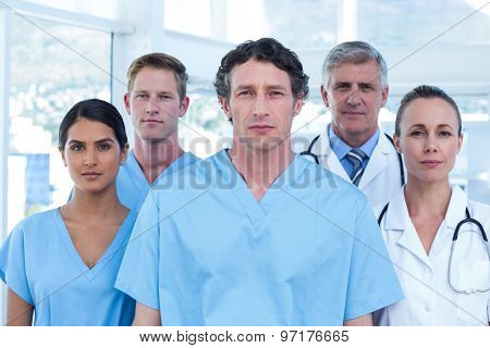 Team of serious doctors looking at camera in the meeting room