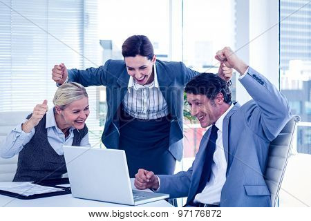 Business people cheering at laptop in the office