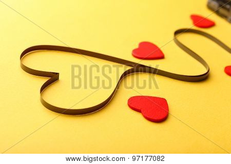 Magnetic tape in shape of heart on yellow background