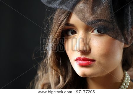 Retro style portrait of young woman on dark background