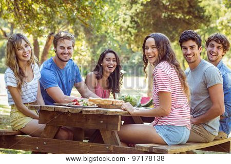 Happy friends in the park having lunch on a sunny day
