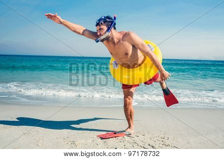Man wearing flippers and rubber ring at the beach on a sunny day