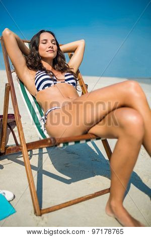 Pretty brunette relaxing on deck chair at the beach on a sunny day