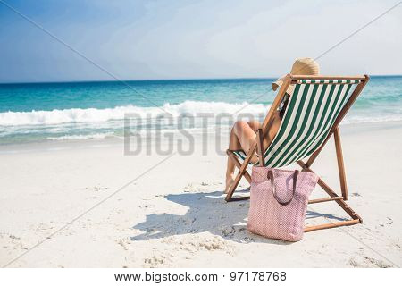 Rear view of pretty brunette relaxing on deck chair at the beach on a sunny day