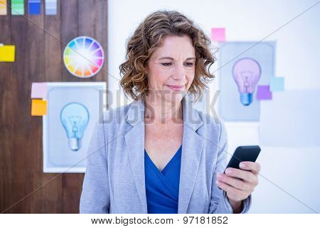 Creative businesswoman using her smartphone in office