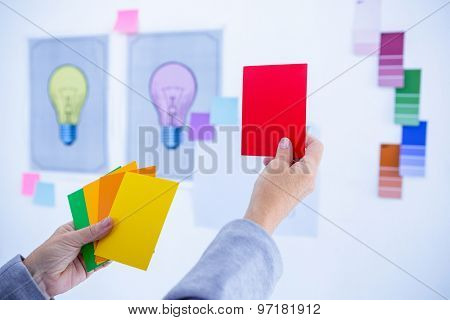 Creative businesswoman holding color cards in office